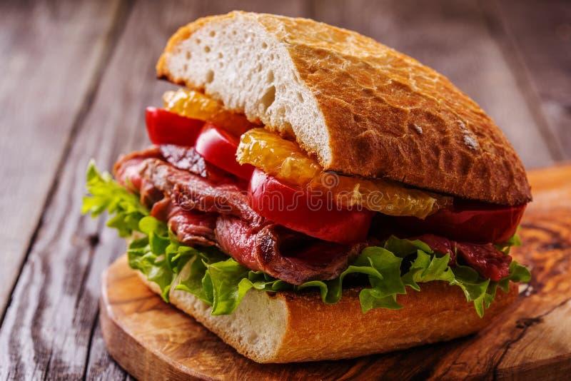 Soczysta stek kanapka z warzywami i plasterkami pomarańcze fotografia royalty free