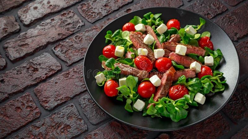 Soczysta wołowiny polędwicy stku sałatka z pomidorami, feta serem i zieleni warzywami w czarnym talerzu piec, zdrowa żywność zdjęcie royalty free