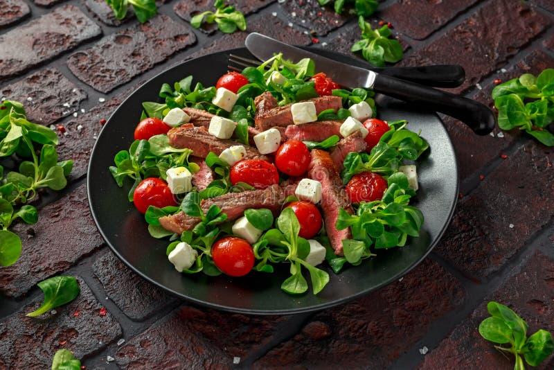 Soczysta wołowiny polędwicy stku sałatka z pomidorami, feta serem i zieleni warzywami w czarnym talerzu piec, zdrowa żywność zdjęcia stock