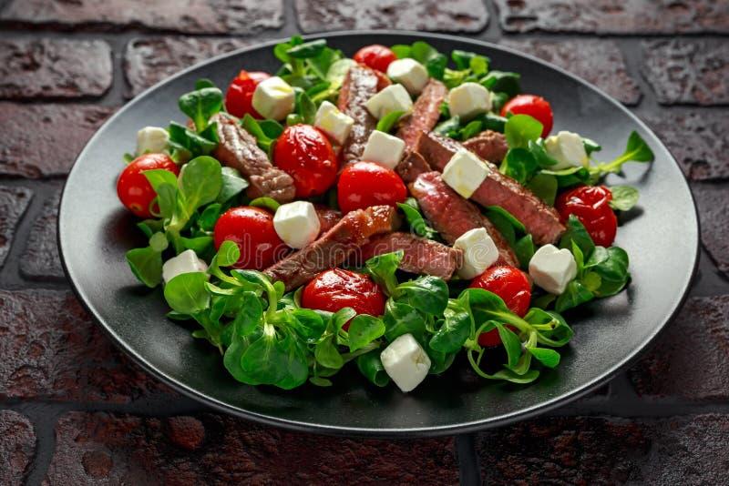Soczysta wołowiny polędwicy stku sałatka z pomidorami, feta serem i zieleni warzywami w czarnym talerzu piec, zdrowa żywność fotografia stock