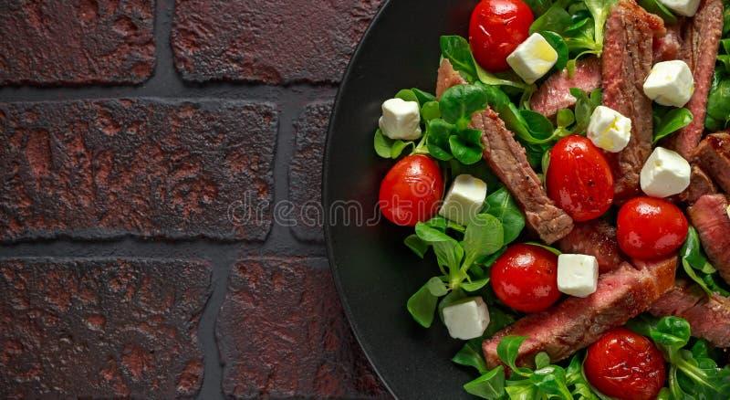Soczysta wołowiny polędwicy stku sałatka z pomidorami, feta serem i zieleni warzywami w czarnym talerzu piec, zdrowa żywność zdjęcia royalty free