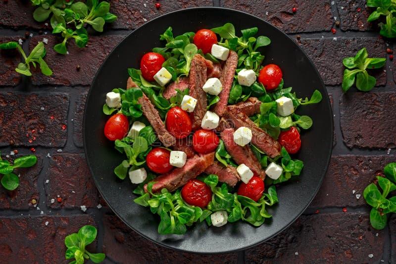 Soczysta wołowiny polędwicy stku sałatka z pomidorami, feta serem i zieleni warzywami w czarnym talerzu piec, zdrowa żywność obrazy royalty free