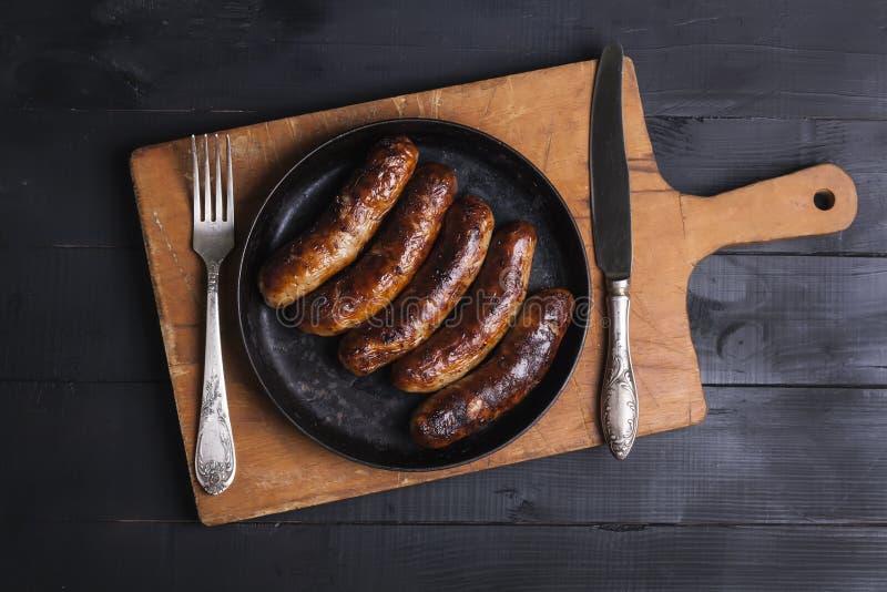 Soczyste piec na grillu kurczak kiełbasy na ciemnym drewnianym tle fotografia stock