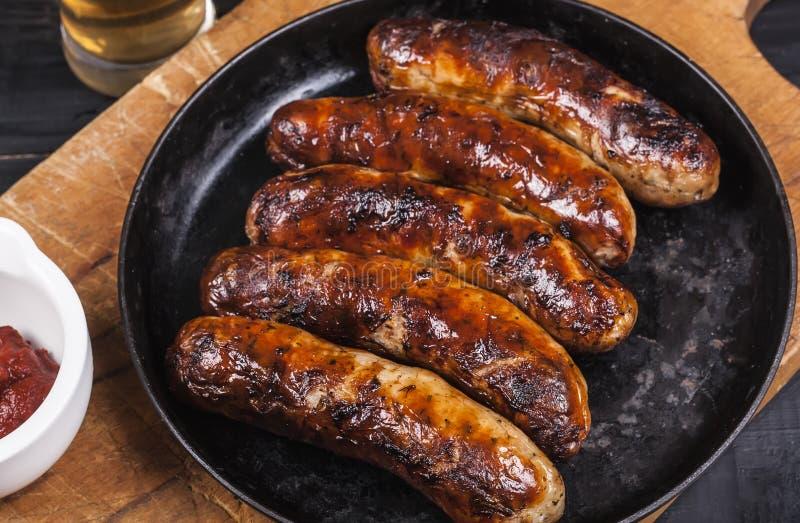 Soczyste piec na grillu kurczak kiełbasy na ciemnym drewnianym tle obraz royalty free
