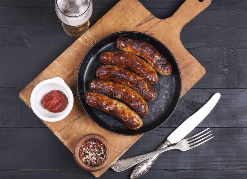 Soczyste piec na grillu kurczak kiełbasy na ciemnym drewnianym tle zdjęcia royalty free