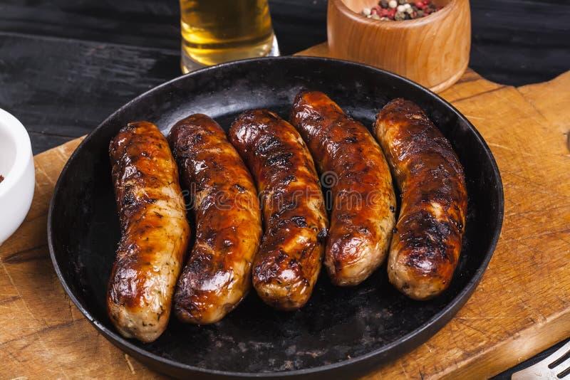 Soczyste piec na grillu kurczak kiełbasy na ciemnym drewnianym tle fotografia royalty free