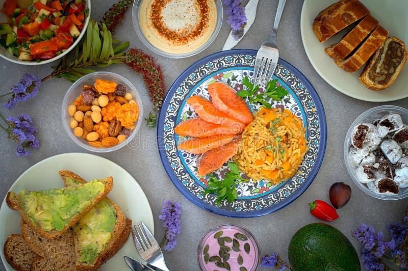 Soczyste porcje polędwicowy łosoś słuzyć z ryż, jarzynowa sałatka, hummus, dokrętki, avocado kanapki, czekoladowi cukierki, dokrę zdjęcie royalty free