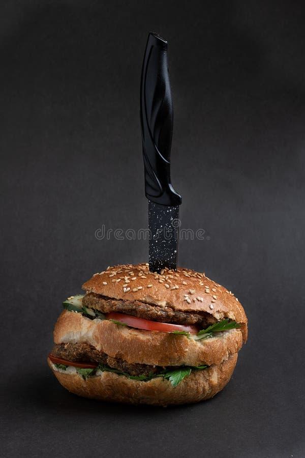 Soczysty duży cheeseburger z pieczarkami i warzywami, nóż wśrodku Selekcyjna ostro?? zdjęcie royalty free