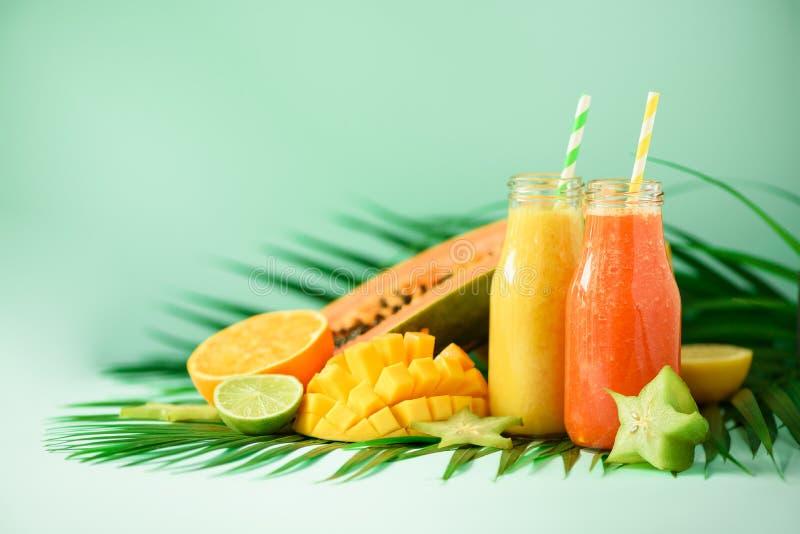 Soczysty melonowiec i ananas, mango, pomarańczowy owocowy smoothie w dwa słojach na turkusowym tle Detox, lato diety jedzenie fotografia royalty free