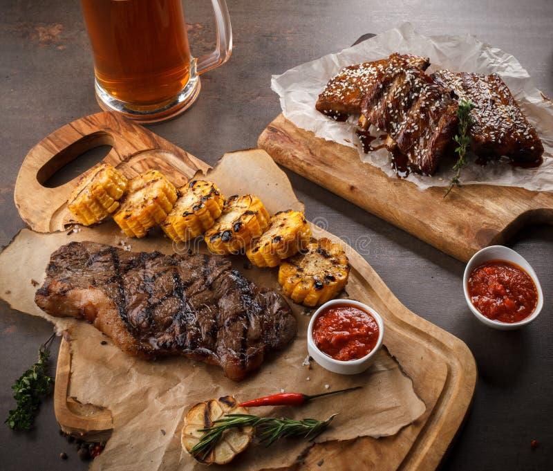 Soczysty stek na grillu Z rozmarynami, czosnkiem, chili i kukurudzą na chlebie na i grillu drewnianej desce i BBQ części zapasowe fotografia stock