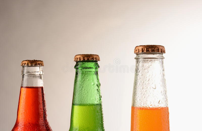 Soda Bottles. Three different soda bottles covered with condensation. Horizontal format with a warm light to dark background. Sodas are; Strawberry, orange, and royalty free stock photography