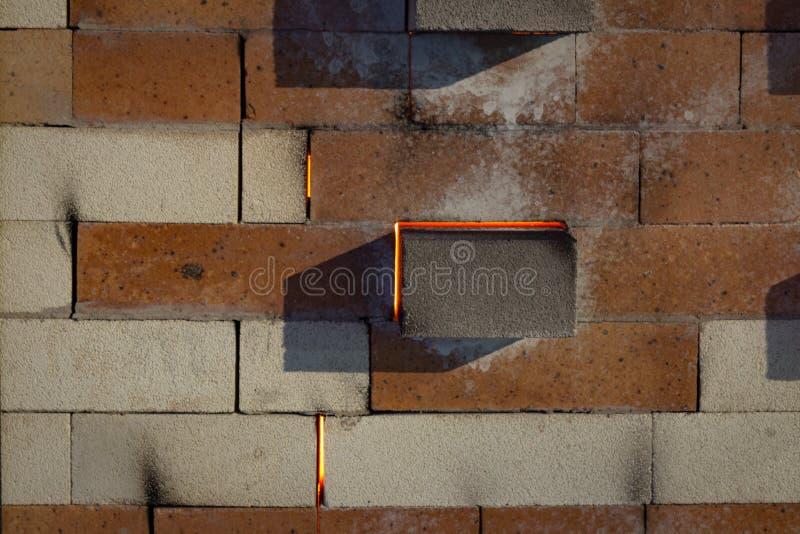 Soda die rond ruimten tussen bakstenen in een sodaoven lekken met duidelijke gloed van actief vuren stock afbeelding