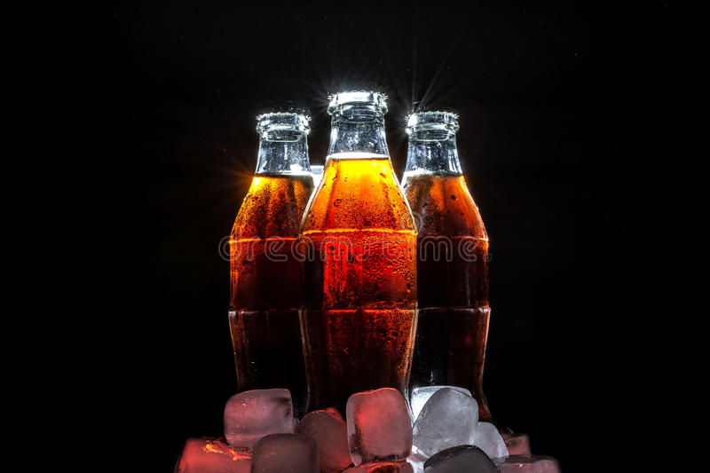 Soda glass bottles in ice cube with beautiful reflection and patches of sunlight on black royalty free stock photo
