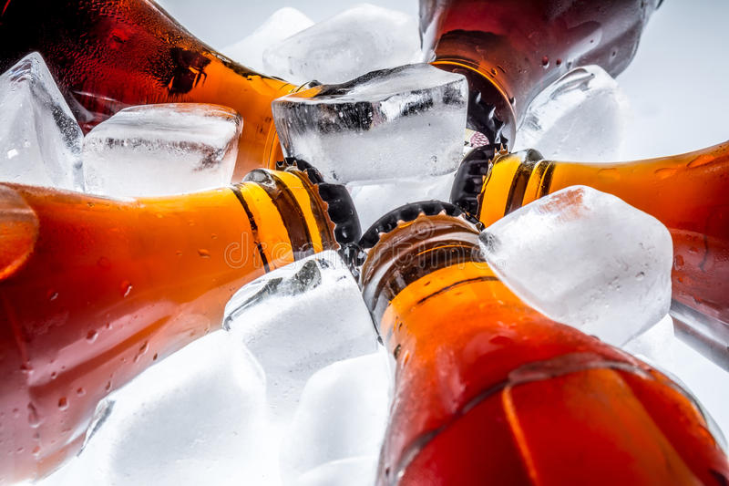 Soda glass bottles in a refrigerated ice cubes on light background. Soda glass bottles in a refrigerated ice cubes on a light background stock image