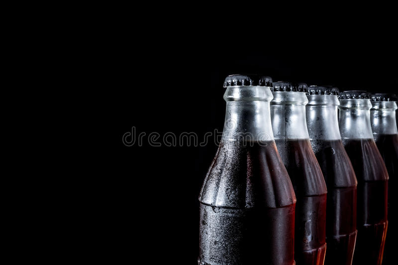 Soda glass bottles standing in a row isolated on a black. Background stock photo