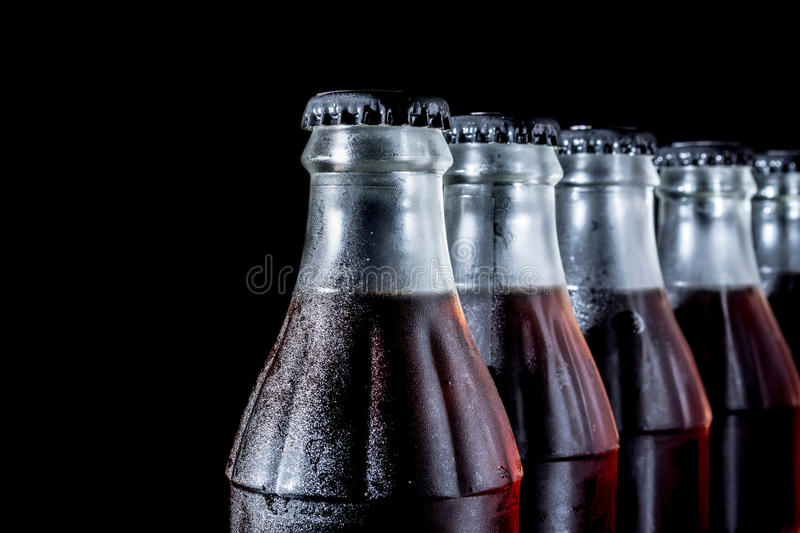 Soda glass bottles standing in a row isolated on a black. Background royalty free stock image