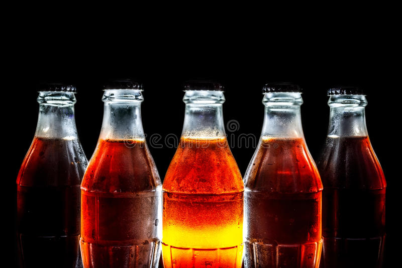 Soda glass bottles standing in a row isolated on a black. Background stock photography