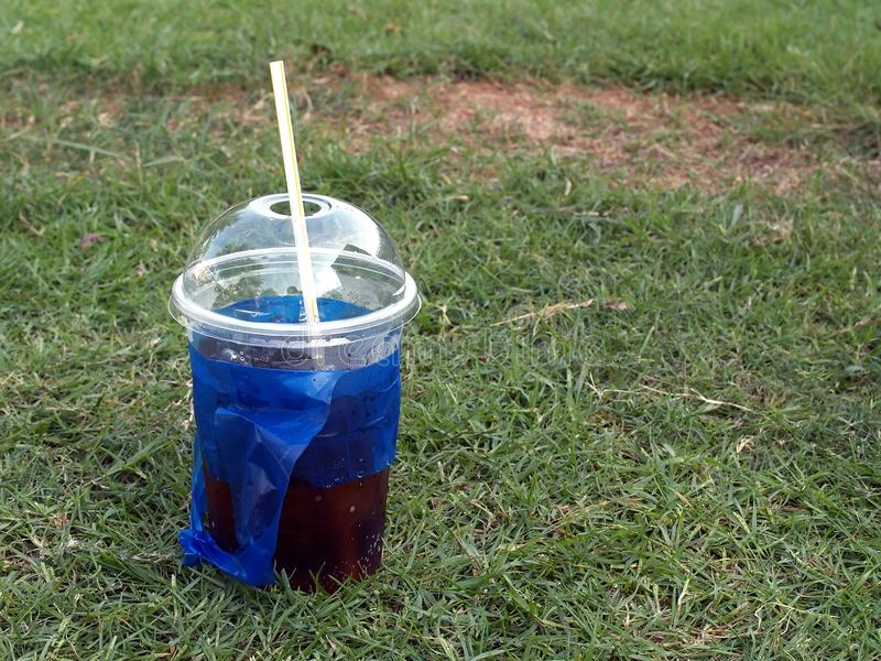 Close-up soda pop in transparent plastic cup with white straw and blue bag on green grass field. Soda pop in transparent plastic cup with white straw and blue royalty free stock photography