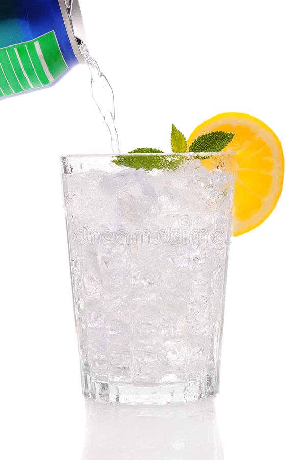 Soda pouring from a can into a glass. Clear Soda pouring from a can into a glass filled with Ice with a lemon wedge and mint sprig. Vertical format isolated stock photography