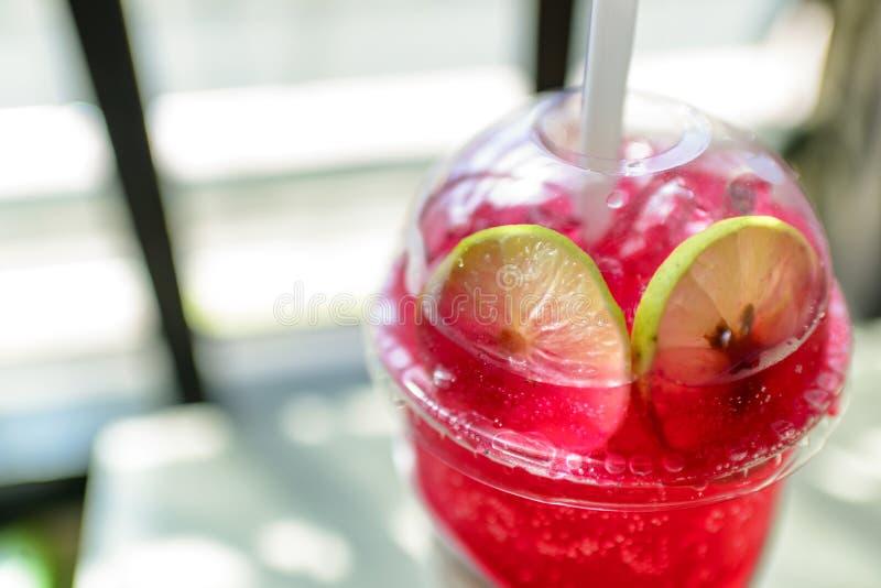 Soda roja, vidrio claro, limón, imagen de archivo
