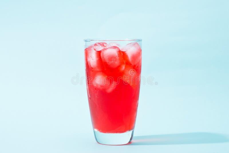 soda Rotes funkelndes Wasser mit Eis in einem Glas stockfotografie