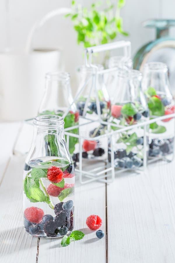 Soda scintillante in bottiglia con le bacche e le foglie di menta fotografia stock