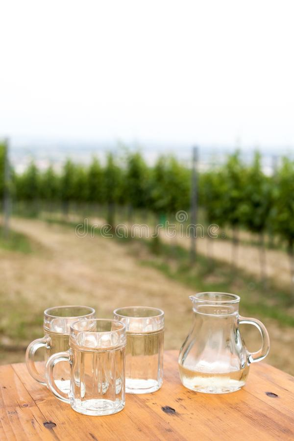 Soda spritzer drink refreshment. Three Glass cup of white wine, decanter on wooden table on backgrounds of Vineyards in Heuriger t. Avern in Eastern Austria royalty free stock photo