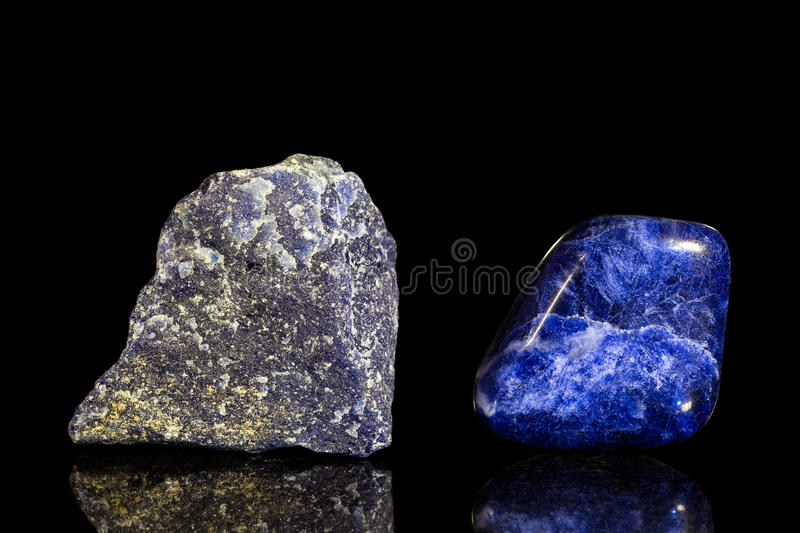 Sodalite, uncut and Tumble finishing. With black background and reflection royalty free stock photography