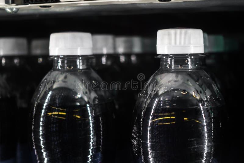 Sodavattenflaskor i flytande R för vita kapsyler för varuautomat svart royaltyfri fotografi