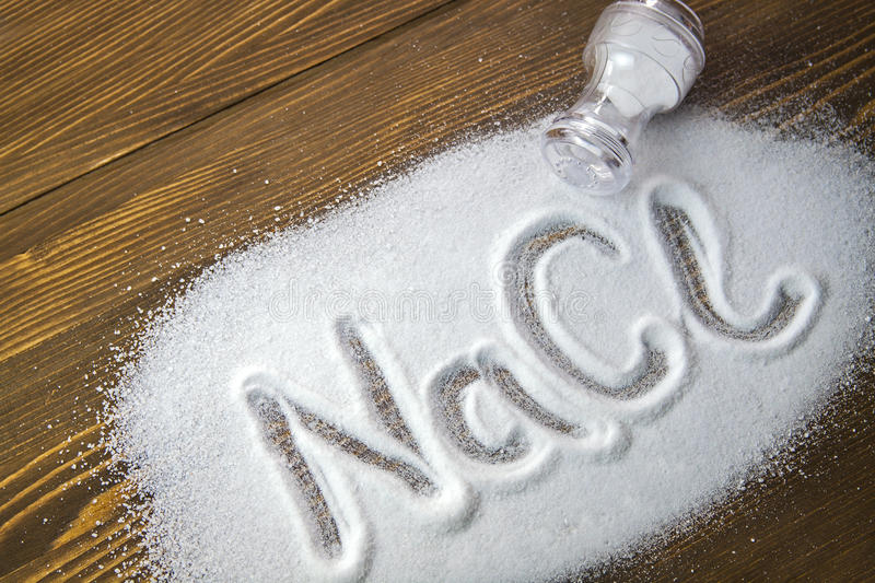 Sodium Chloride - Salt. NaCl written on a heap of salt - Sodium Chloride stock photography