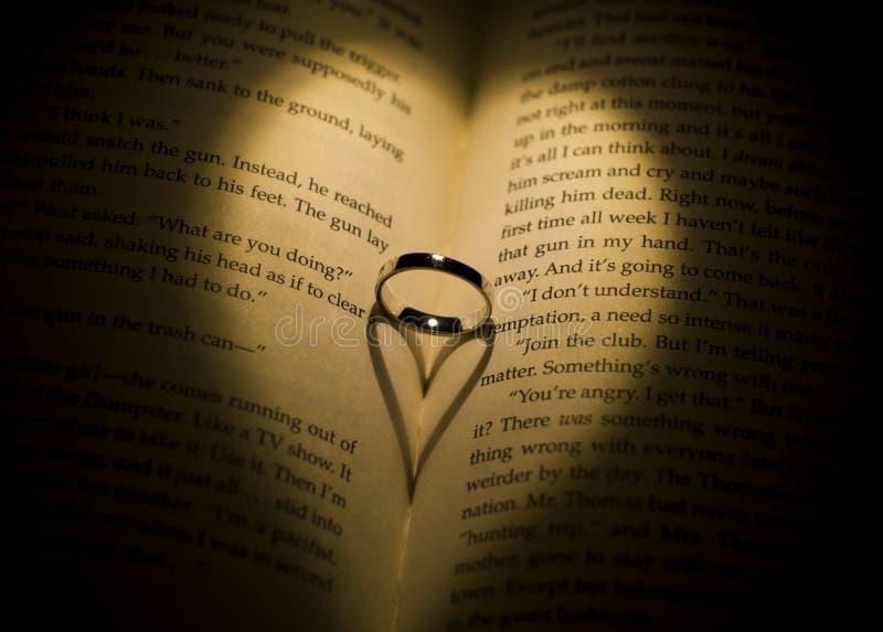 Soe moldando uma sombra heart-shaped em um livro imagem de stock