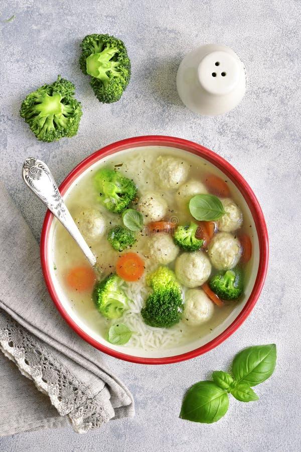 Soep met kippenvleesballetjes, rijst, broccoli en groene erwt bovenkant vi stock afbeeldingen
