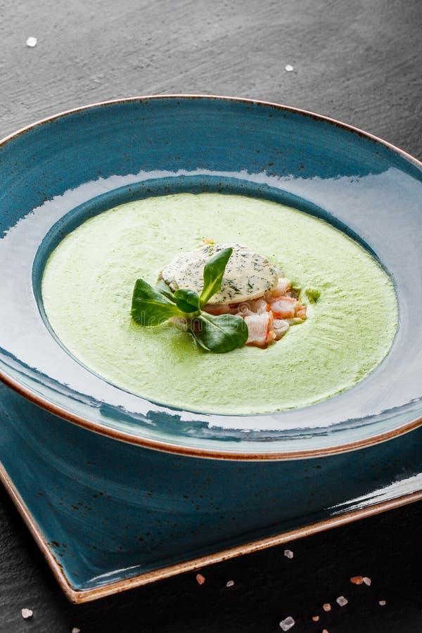 Soep van de broccoli de groene room met garnalen en kaas in plaat op donkere steenachtergrond Het schone eten, gezond voedselconc stock foto's