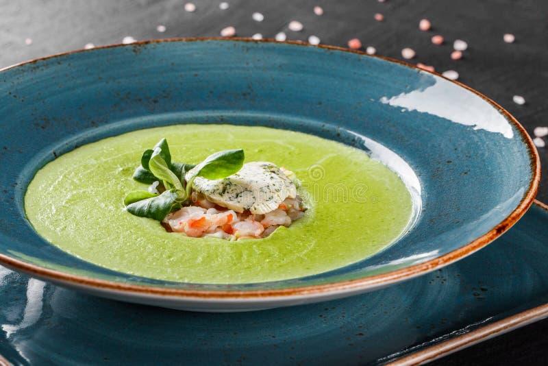 Soep van de broccoli de groene room met garnalen en kaas in plaat op donkere steenachtergrond Het schone eten, gezond voedselconc stock foto