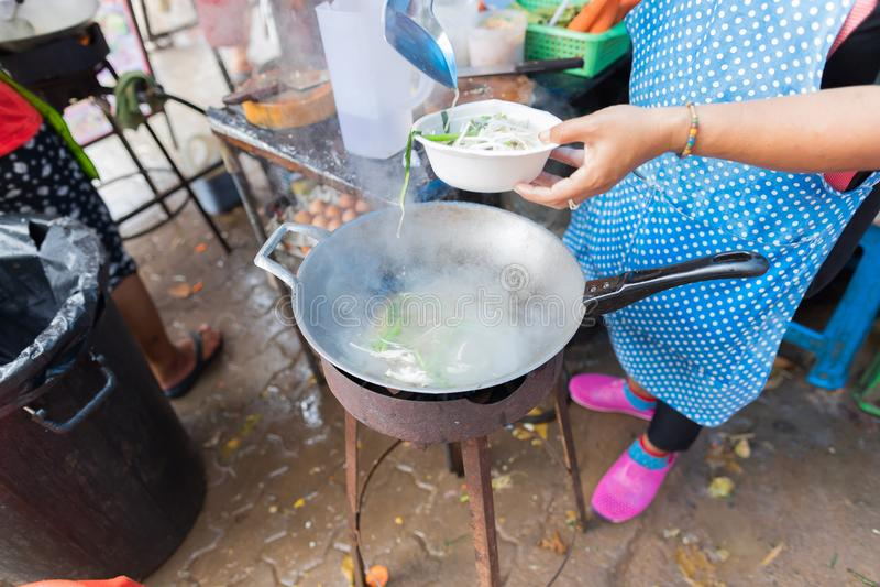 Soep van de vrouwen de Kokende Noedel in openlucht op Traditionele Straatmarkt in het Voedsel die van Azië op Open Bazaar voorber royalty-vrije stock fotografie