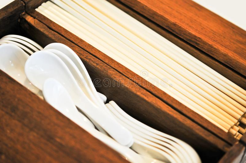 Soeplepels en eetstokjes in houten geval stock foto