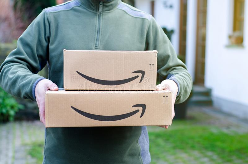 Soest, Germany - January 14, 2019:  Man delivers Amazon Prime package. Man delivers Amazon Prime package royalty free stock photography