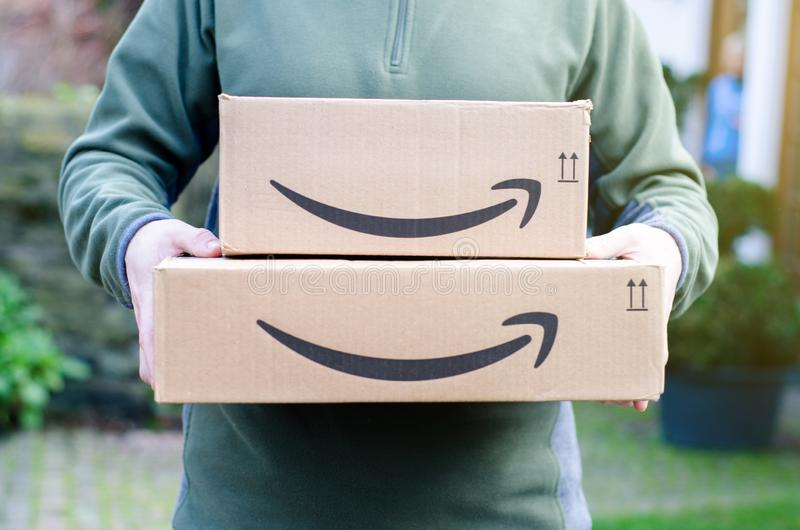 Soest, Germany - January 14, 2019:  Man delivers Amazon Prime package. Man delivers Amazon Prime package royalty free stock photos