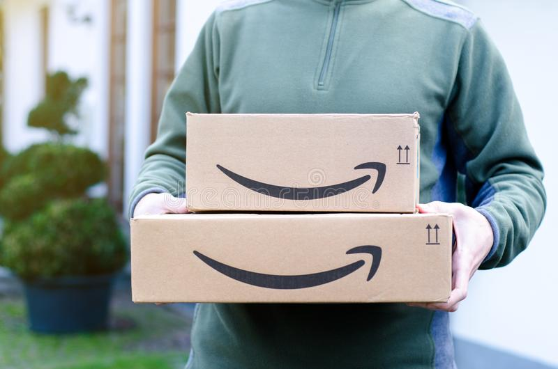 Soest, Germany - January 14, 2019:  Man delivers Amazon Prime package. Man delivers Amazon Prime package stock images