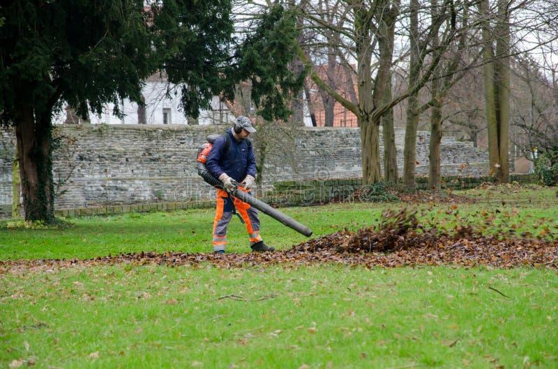 Soest Tyskland - December 18, 2017: Mannen med dammsugare är att göra ren parkerar från sidorna arkivbilder