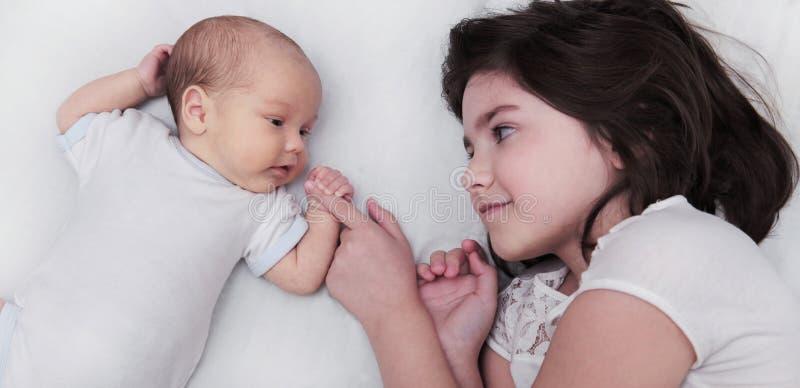 Soeur d'enfants de mêmes parents avec le frère nouveau-né de bébé image stock