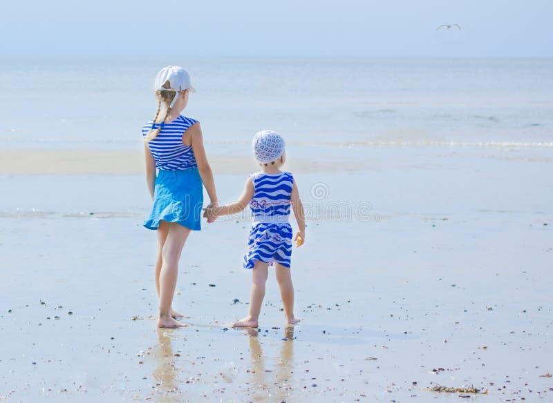 Soeur deux sur le bord de la mer examinant la distance photographie stock libre de droits