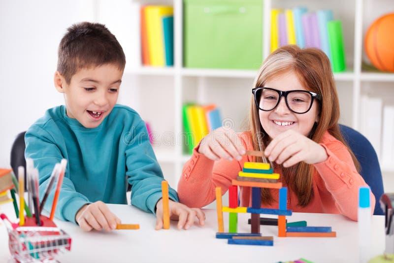 Soeur plus âgée de sourire jouant avec le petit frère avec le blo en bois photos stock
