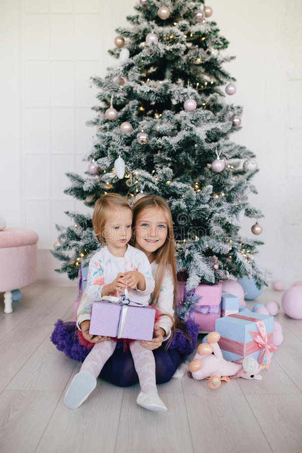 Soeurs à la maison avec l'arbre et les présents de Noël Portrait des filles heureuses d'enfants avec des boîte-cadeau et des déco photos stock