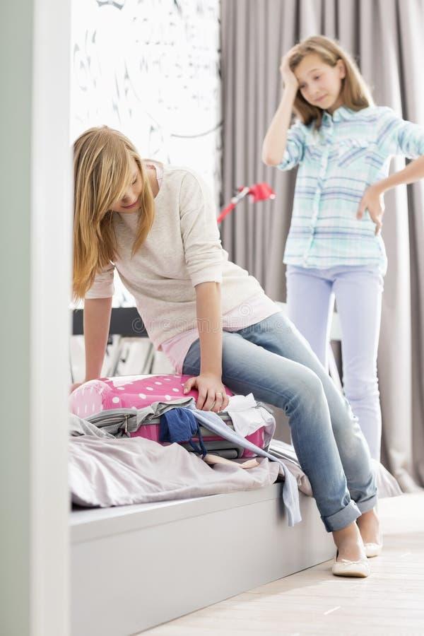 Soeurs essayant de fermer la valise à la maison image libre de droits