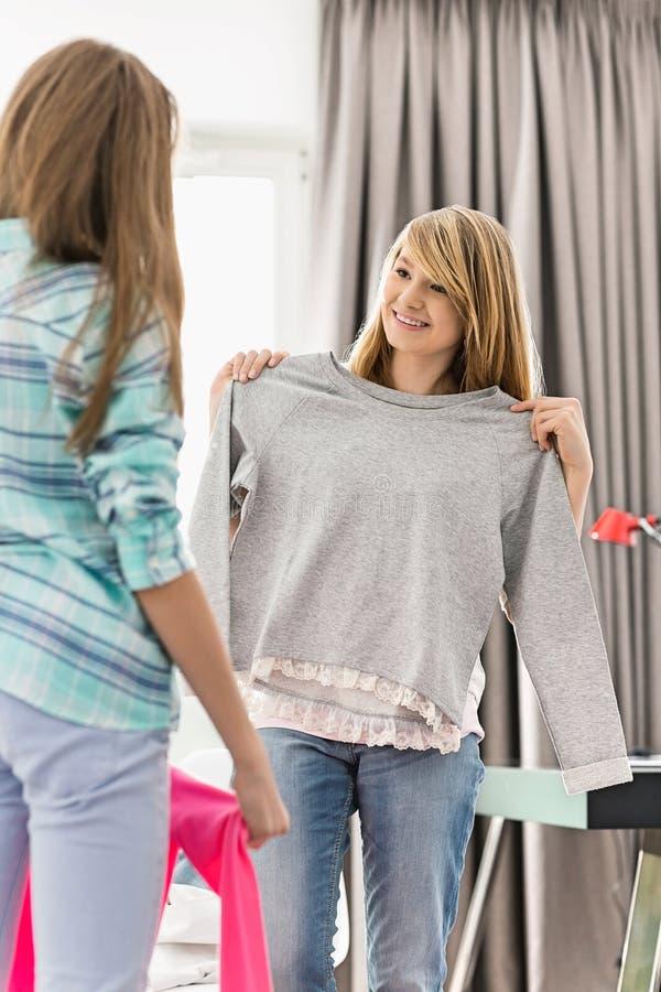 Soeurs essayant sur des vêtements à la maison photos stock