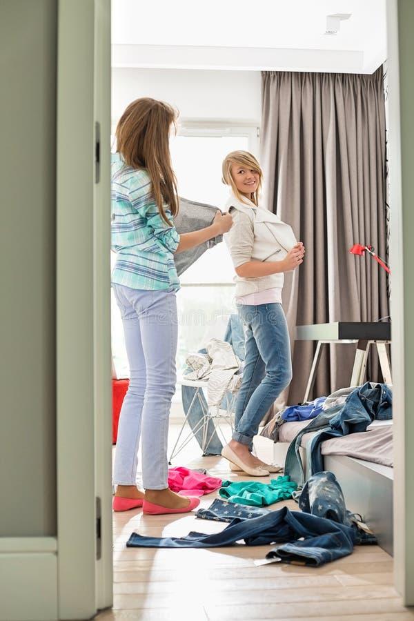 Soeurs essayant sur des vêtements à la maison image libre de droits