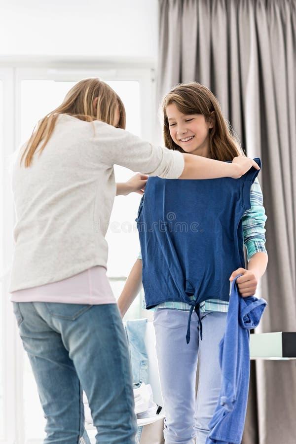 Soeurs essayant sur des vêtements à la maison images libres de droits