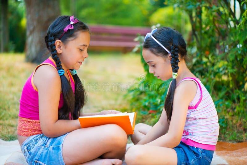 Soeurs hispaniques heureuses lisant en parc images stock