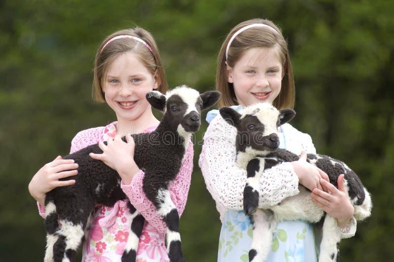 Soeurs jumelles avec l'agneau sur Pâques photos stock